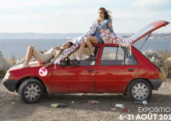jeunes femmes sur une voiture rouge face à la mer